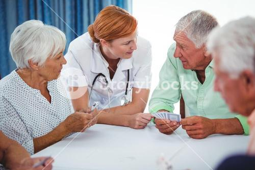 Smiling nurse looking at senior person during a game of cards