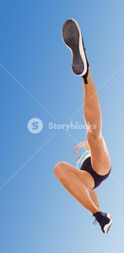 Low angle female athlete jumping