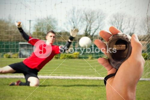 Composite image of coach is holding a stopwatch against goalkeeper