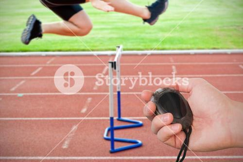 Composite image of coach is holding a stopwatch against assertive male athlete jumping above hedge