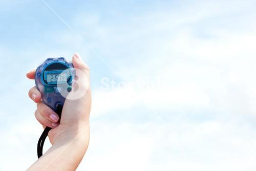 Close-up of a woman holding a chronometer to measure performance against blue sky with clouds