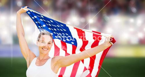 Composite image of portrait of happy sportswoman posing with an american flag