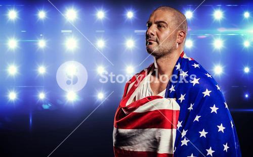 Athlete with england flag wrapped around his body against composite image of blue spotlight
