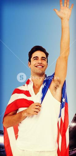 Athlete with american flag wrapped around his body against composite image of astadium