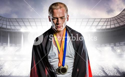 Composite image of athlete with german flag wrapped around his body