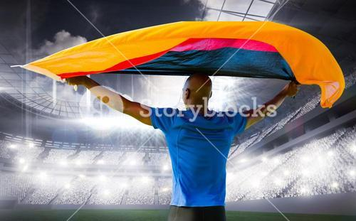 Composite image of sporty man holding a german flag