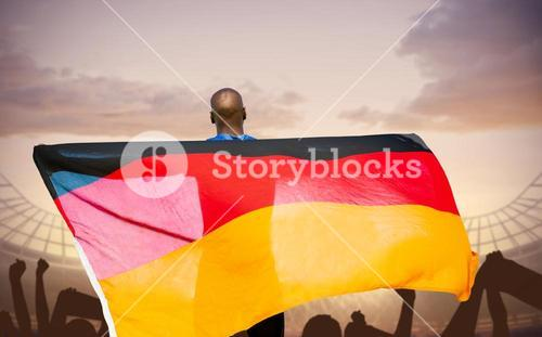 Composite image of rear view of sportsman is holding a German flag