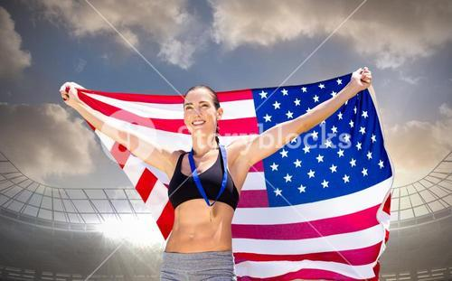 Composite image of happy sportswoman posing with an american flag and medal