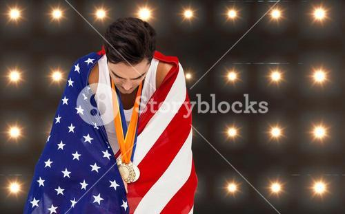 Composite image of athlete with gold medals and american flag looking down