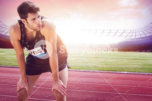 Athletic man resting with hands on knees