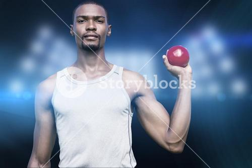 Composite image of portrait of serious sportsman is holding a shot put