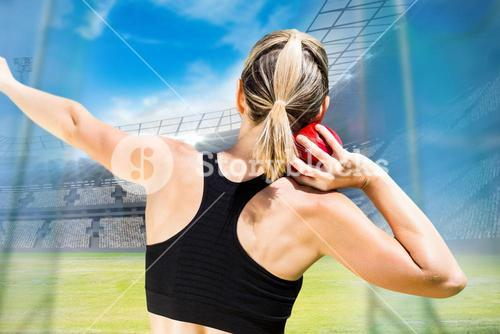 Composite image of rear view of sportswoman is practising shot put