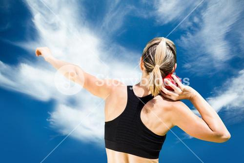 Composite image of rear view of sportswoman practicing shot put