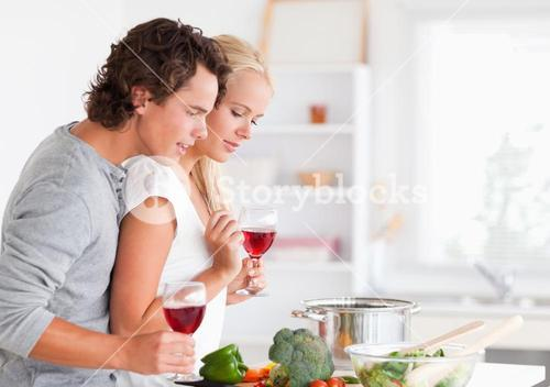 Couple cooking while having a glass of wine
