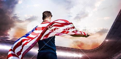 Composite image of rear view of sportsman holding an american flag