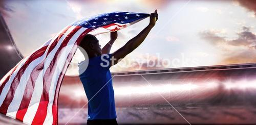 Composite image of rear view of sportsman raising an american flag
