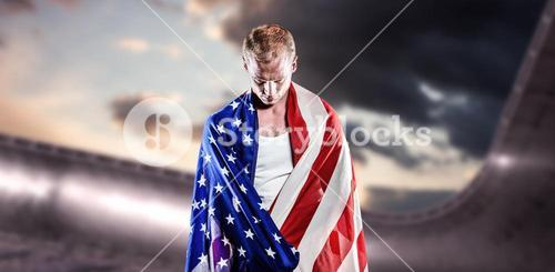 Composite image of athlete with american flag wrapped around his body