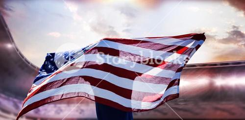 Composite image of rear view of sportsman posing with an american flag