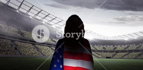 Composite image of rear view of sporty woman holding an american flag