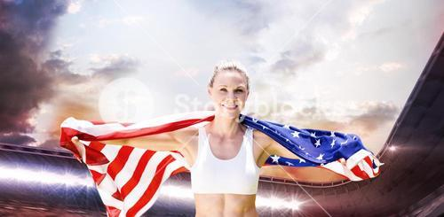 Composite image of portrait of smiling sportswoman posing with an american flag