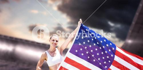 Composite image of happy sportswoman holding an american flag