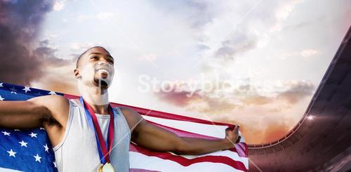 Composite image of portrait of happy sportsman posing with an american flag
