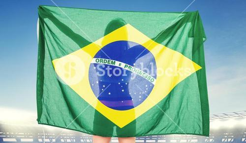 Composite image of athlete posing with brazilian flag after victory
