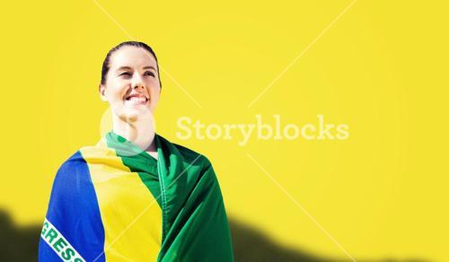 Composite image of sporty woman holding brazilian flag