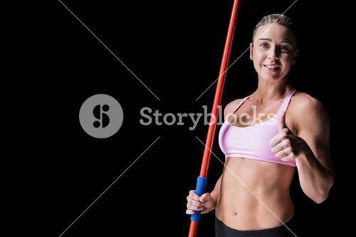 Composite image of female athlete holding a javelin and showing a thumbs up