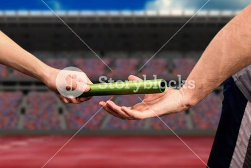 Composite image of man passing the baton to partner on track