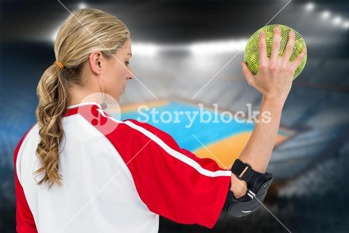Composite image of sportswoman holding a ball