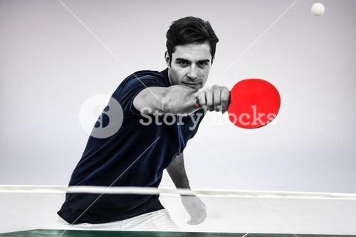 Composite image of portrait of male athlete playing table tennis