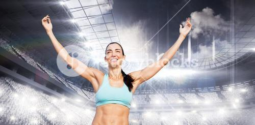 Composite image of portrait of happy sportswoman is raising arms