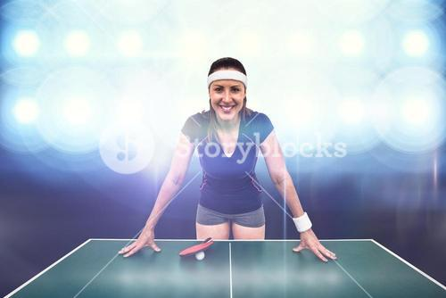 Composite image of happy female athlete leaning on hard table