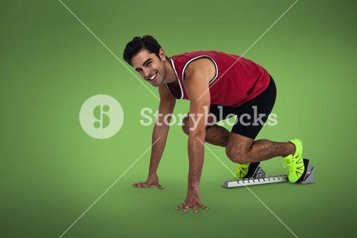 Composite image of male athlete is smiling in the starting blocks