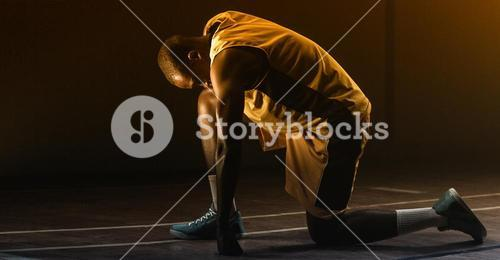 Basketball player preparing to play with knee on the floor and head lowered