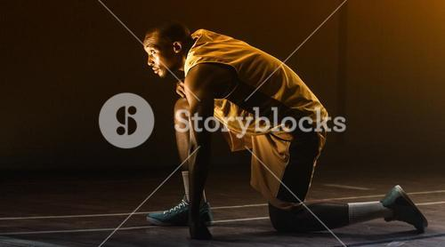Basketball player preparing to play with knee on the floor and looking up