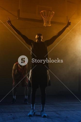 Victorious basketball player raising his arms up