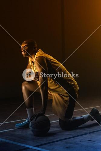 Portrait of basketball player with a knee on the floor and a hand on the ball looking up