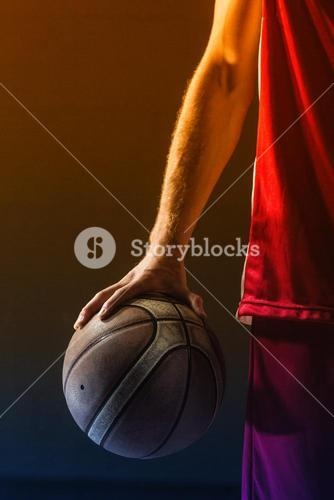 Close up on basketball held by basketball player