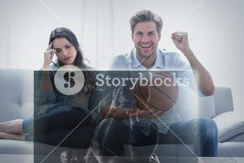 Composite image of man watching sport on television next to his bored wife