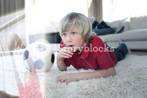 Composite image of cute boy watching soccer match
