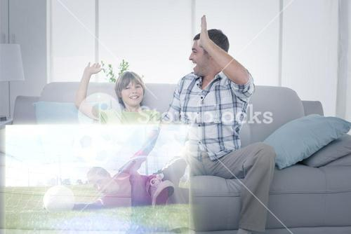 Composite image of father and son giving high-five in front of soccer match on television