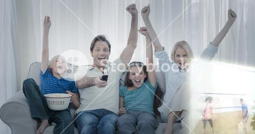 Composite image of family watching sport on television and raising arms