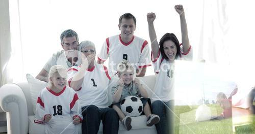 Composite image of happy family watching a football match in television