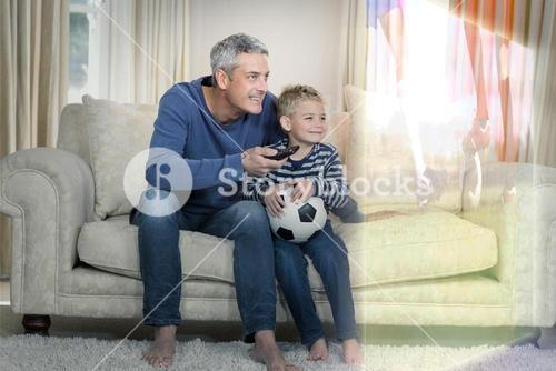 Composite image of father and son are watching sport match on television