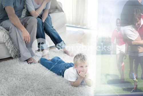 Composite image of cute boy lying on carpet is watching sport on television in front of his parents