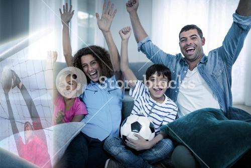 Composite image of family watching sport match on television and raising arms