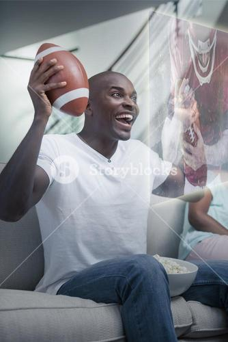 Composite image of happy man is watching sport on television