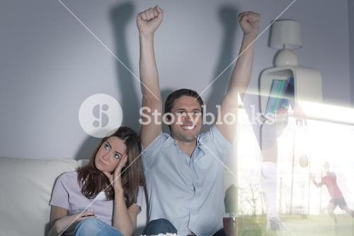 Composite image of man is watching sport on television next to his bored wife